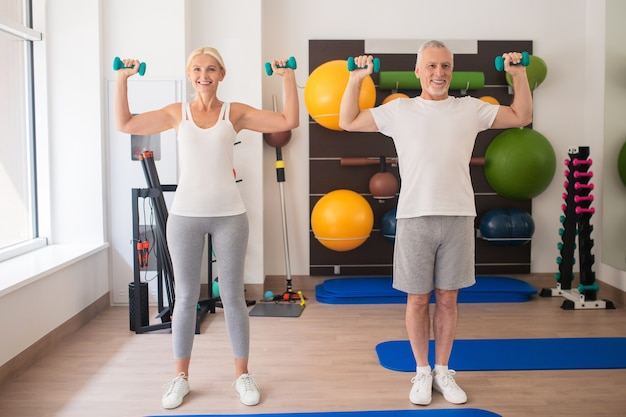 Positiver mann und frau, die mit hanteln trainieren und ihre arme heben