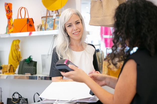 Positiver modegeschäftskunde, der für den kauf an der kasse zahlt und das pos-terminal und die kassiererhände betrachtet. mittlere aufnahme, kopierraum. einkaufskonzept