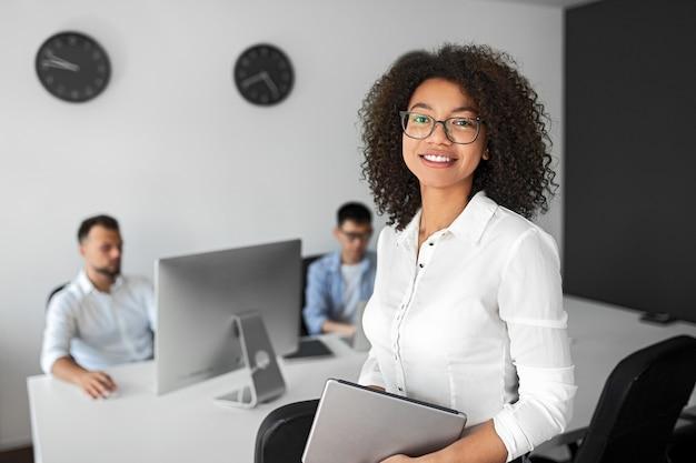 Positiver moderner weiblicher manager im formellen weißen hemd und in den brillen, die tablette halten und kamera betrachten, während im modernen büro mit arbeiten an computerkollegen stehen