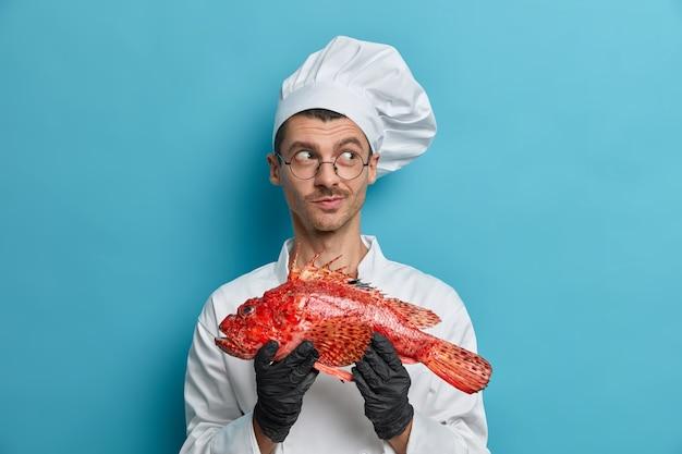 Positiver, nachdenklicher männlicher koch hält großen ungekochten fisch, überlegt, was er zum abendessen kochen soll, wählt gesunde meeresfrüchte und delikatessen