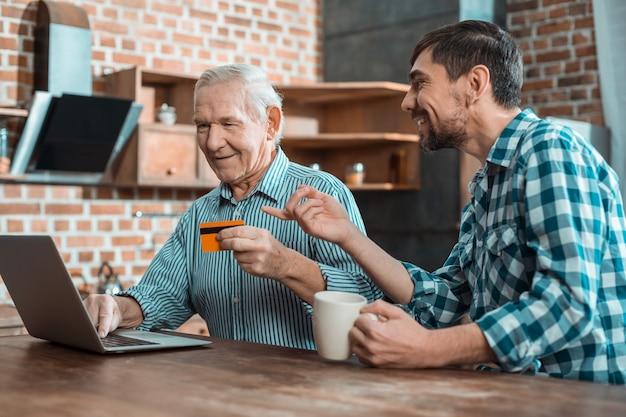 Positiver netter alter mann, der eine kreditkarte hält und lernt, wie man eine online-zahlung macht, während er mit seinem sohn zusammen ist