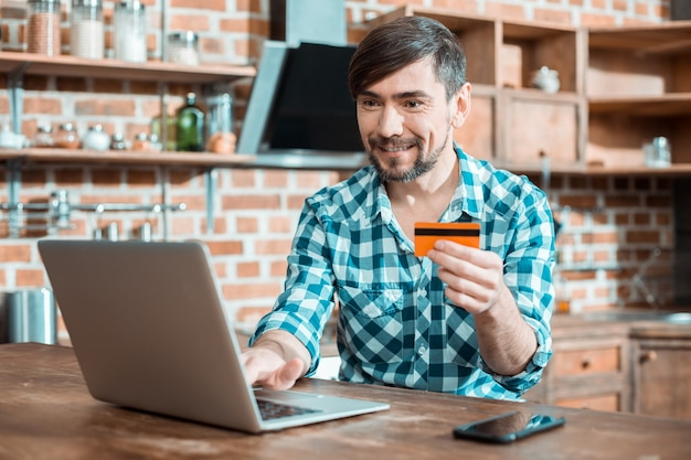 Positiver netter gut aussehender mann, der seinen laptop benutzt und lächelt, während er eine überweisung macht