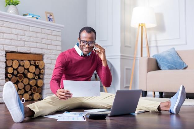 Positiver netter hart arbeitender mann, der auf dem boden sitzt und die dokumente betrachtet, während er einen anruf tätigt