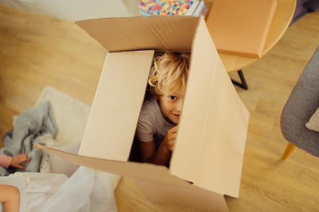 Positiver netter junge, der sich in einer kiste versteckt