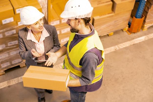 Positiver netter mann, der mit seiner klientin spricht, während er ihr das paket liefert