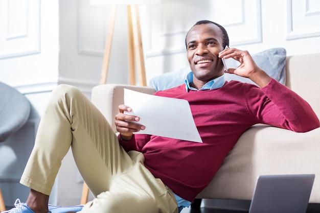 Positiver netter selbständiger mann, der ein dokument hält und anruft, während er mit der arbeit beschäftigt ist