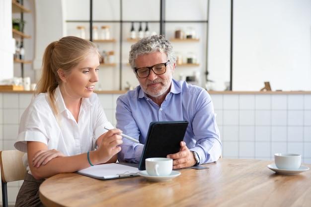 Positiver reifer männlicher mentor, der dem praktikanten die arbeitsdetails erklärt