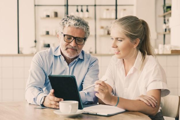 Positiver reifer männlicher mentor, der dem praktikanten die arbeitsdetails erklärt.