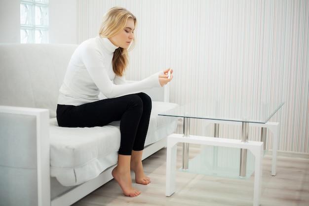 Positiver schwangerschaftstest. porträt der hoffnungslosen jungen frau, die schwangerschaftsteststock hält