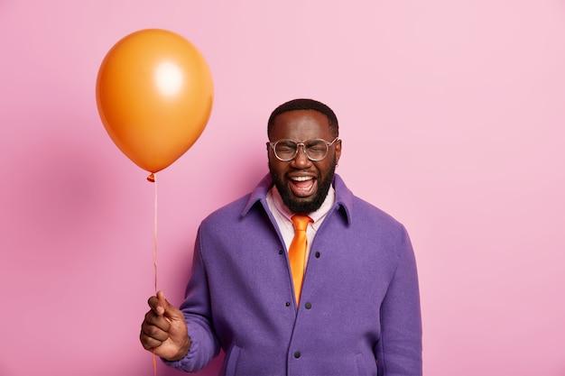Positiver schwarzer mann mit bart hält aufgeblasenen orangefarbenen ballon in der hand, ruft emotional aus und geht auf party