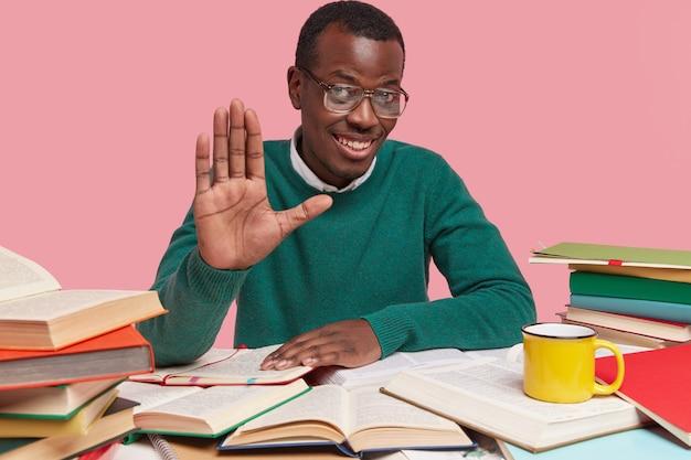 Positiver schwarzer mann zeigt handfläche, sieht optimistisch aus, grüßt mit kollegen oder gruppenmitgliedern, sieht freundlich aus, sitzt am desktop, liest dokumentation