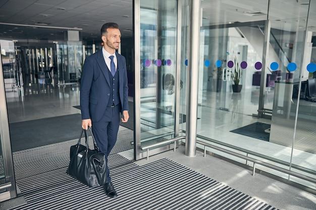 Positiver, selbstbewusster geschäftsmann, der das gepäck trägt und lächelt, während er den flughafen nach seiner ankunft verlässt
