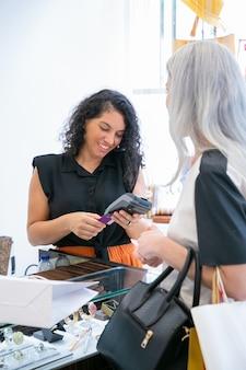 Positiver shop-kassierer oder verkäufer im gespräch mit dem kunden und betrieb des zahlungsvorgangs mit pos-terminal und kreditkarte. mittlerer schuss. einkaufs- oder kaufkonzept