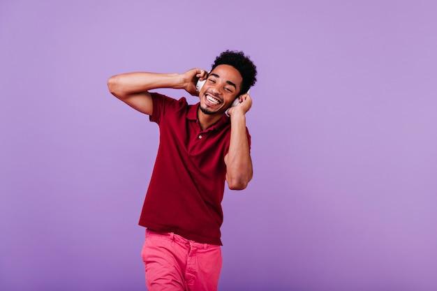 Positiver sorgloser mann, der lacht, während er lied genießt. gut gekleideter kerl, der lächelt und seine kopfhörer berührt.