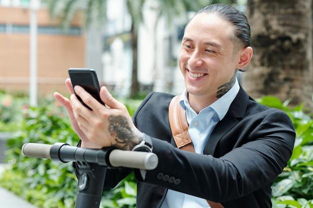 Positiver stilvoller geschäftsmann der gemischten rasse, der nachrichten im smartphone prüft, nachdem er auf roller gefahren wird