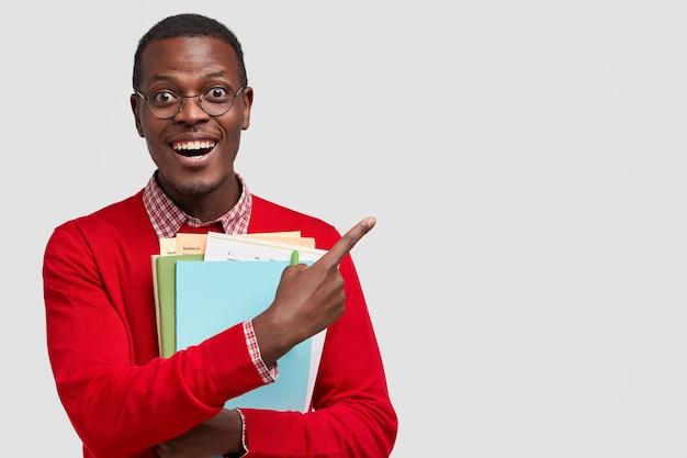 Positiver student hat dunkle haut, trägt ordner und buch, zeigt punkte mit fröhlichem ausdruck beiseite, hat ein zahniges lächeln