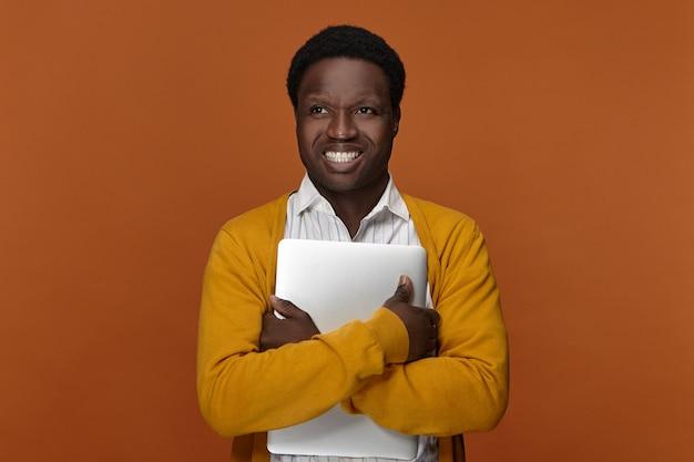 Positiver talentierter junger männlicher freiberufler des afrikanischen aussehens, der tragbaren computer trägt, glücklichen fröhlichen gesichtsausdruck hat, breit lächelt und sein elektronisches hochgeschwindigkeitsgerät genießt