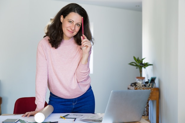 Positiver überzeugter gebäudedesigner an ihrem arbeitsplatz