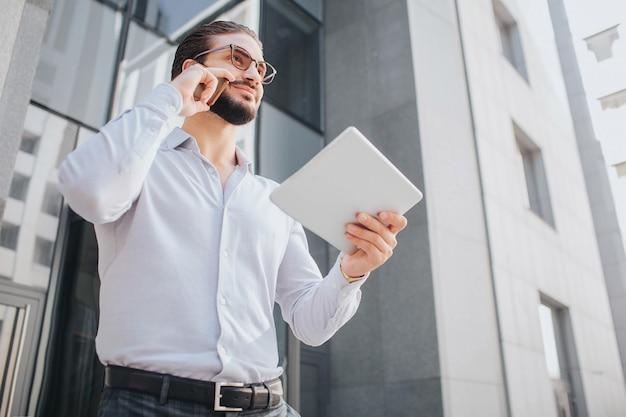 Positiver und fröhlicher junger geschäftsmann steht an hohem gebäude und posiert. er lächelt ein bisschen. guy schaut geradeaus. er telefoniert und hält ein stück papier in der hand.