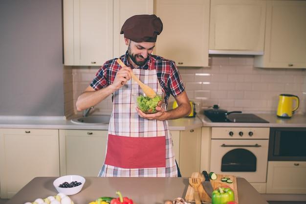 Positiver und glücklicher koch steht in der küche und hält glasschüssel mit salat. er mischte es mit einem holzlöffel. junger mann schaut auf es herab.