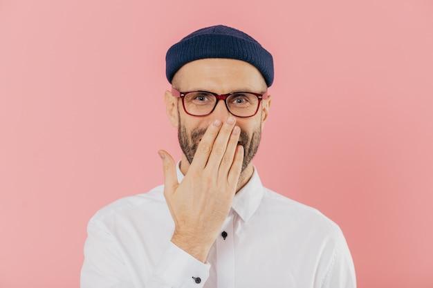 Positiver unrasierter mann bedeckt mund mit palme, kichert positiv, trägt schauspiele