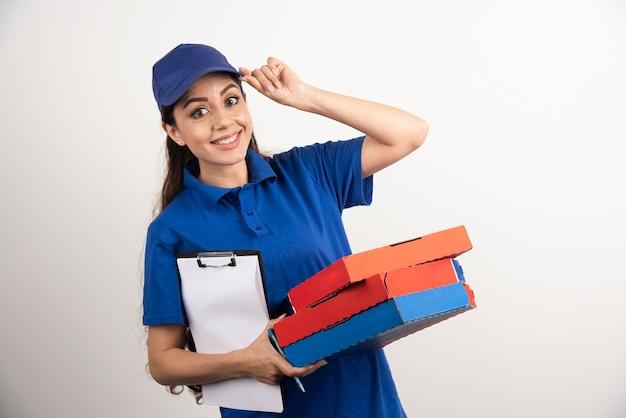 Positiver weiblicher kurier mit pizzakarton und klemmbrett