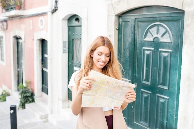 Positiver weiblicher tourist, der papierkarte auf straße verwendet