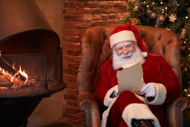 Positiver weißbärtiger weihnachtsmann, der im sessel sitzt und brief vom kind am kamin liest