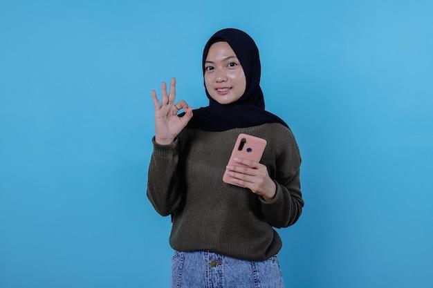 Positives asiatisches frauenmädchen zeigt daumen, bringt smartphone mit, zeigt kopienraum auf leerer blauer wand
