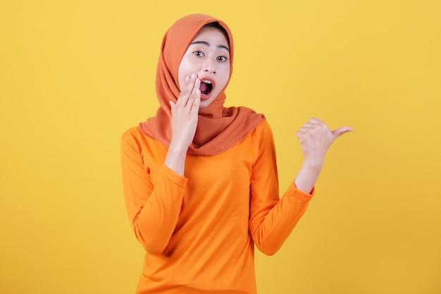 Positives asiatisches frauenmädchen zeigt daumen, zeigt kopienraum auf leerer gelber wand, hat überraschenden ausdruck, trägt lässig hijab, posiert drinnen