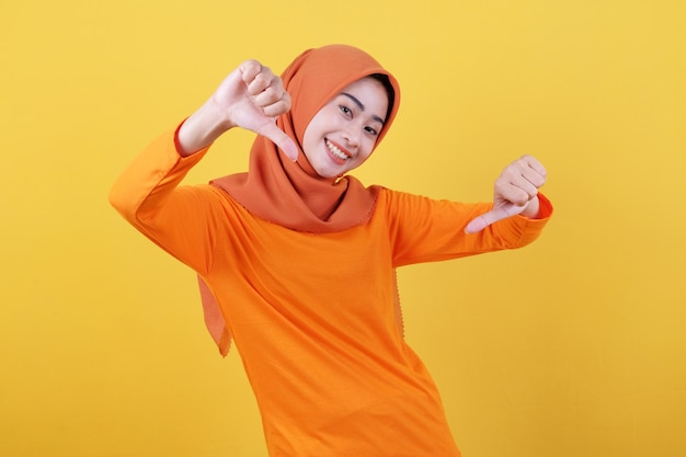 Positives asiatisches frauenmädchen zeigt mit dem daumen nach unten, zeigt kopienraum auf einer leeren gelben wand, hat einen fröhlichen, freundlichen ausdruck, trägt lässig hijab, posiert im innenbereich