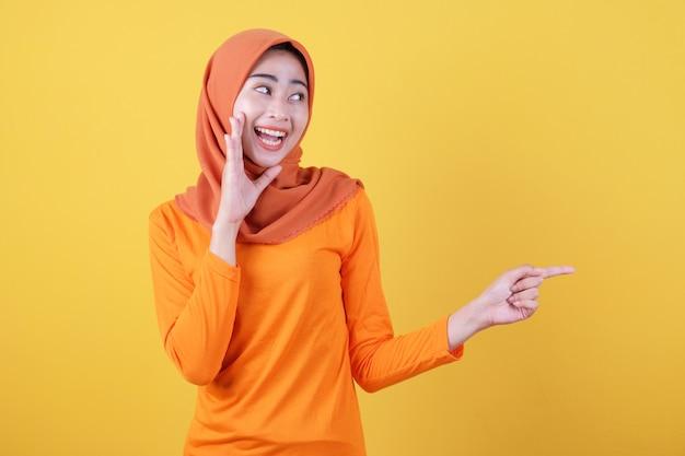 Positives asiatisches frauenmädchen zeigt zeigefinger, zeigt kopienraum auf leerer gelber wand, hat glücklichen freundlichen ausdruck, trägt lässig hijab, posiert drinnen