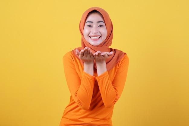 Positives asiatisches mädchen, das auftaucht, zeigt kopienraum auf leerer gelber wand, hat einen glücklichen, freundlichen ausdruck, trägt lässig hijab, posiert im innenbereich