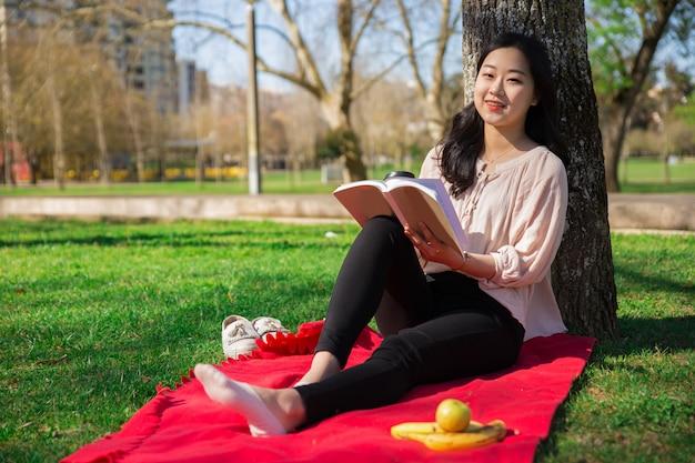 Positives asiatisches mädchen, das interessanten roman im park genießt