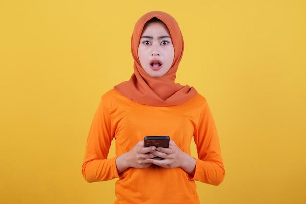 Positives asiatisches mädchen überraschender ausdruck, bringt smartphone mit, zeigt kopienraum auf leerer gelber wand, hat einen fröhlichen, freundlichen ausdruck, trägt lässig hijab, posiert im innenbereich