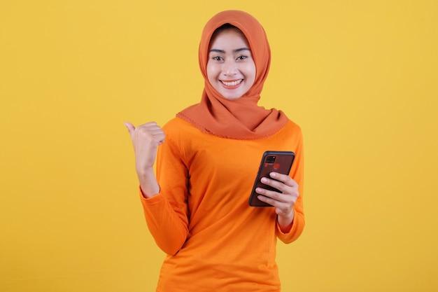 Positives asiatisches mädchen zeigt daumen, bringt smartphone mit, zeigt kopienraum auf leerer gelber wand, hat einen fröhlichen, freundlichen ausdruck, trägt lässig hijab, posiert drinnen
