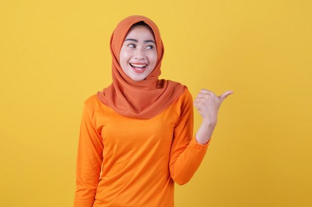 Positives asiatisches mädchen zeigt daumen, zeigt kopienraum auf leerer gelber wand, hat einen glücklichen, freundlichen ausdruck, trägt lässig hijab, posiert im innenbereich