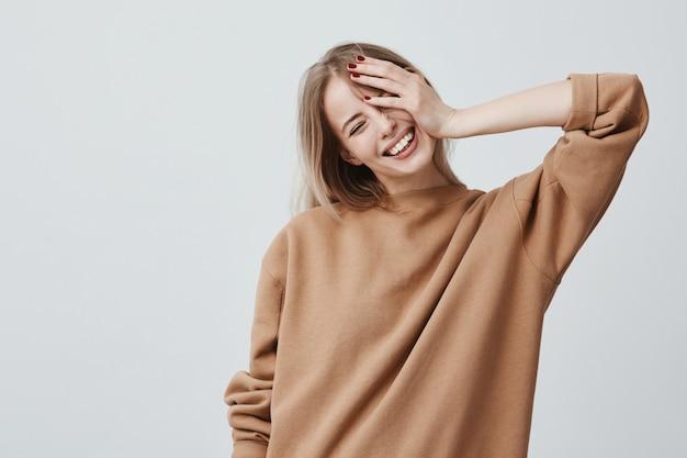 Positives attraktives blondes junges modell trägt lässigen losen pullover und freut sich über gute nachrichten. freudige frau freut sich am wochenende und entspannt sich drinnen