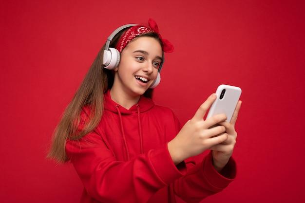 Positives attraktives brünettes mädchen mit rotem hoodie isoliert auf rotem hintergrund hält und verwendet