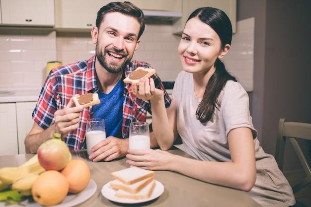 Positives bild des kerls und des mädchens sitzt zusammen am tble und am lächeln. sie gucken. leute halten toast mit schokoladenpaste und gläsern milch. sie sind wunderschön.