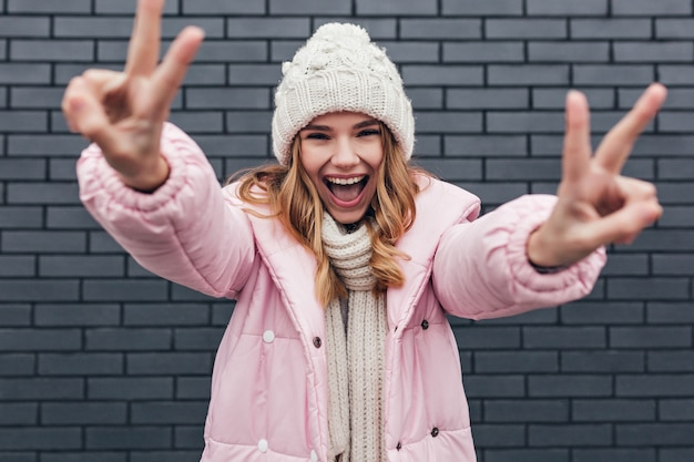Positives blondes mädchen im hut, das glückliche gefühle ausdrückt. inspirierte kaukasische dame in winterkleidung lachend