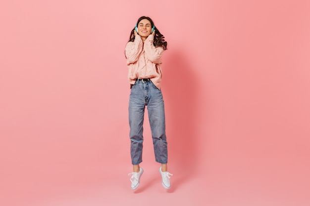 Positives dunkelhaariges mädchen, das lächelt, während musik in blauen kopfhörern hört. frau im gestrickten outfit und in den weißen turnschuhen, die auf rosa hintergrund springen.