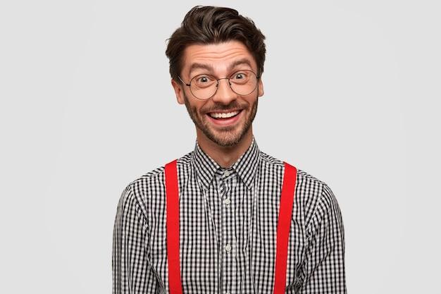 Positives emotionskonzept. bärtiger gutaussehender mann mit breitem strahlendem lächeln, der gute laune hat und einen gut bezahlten job gefunden hat