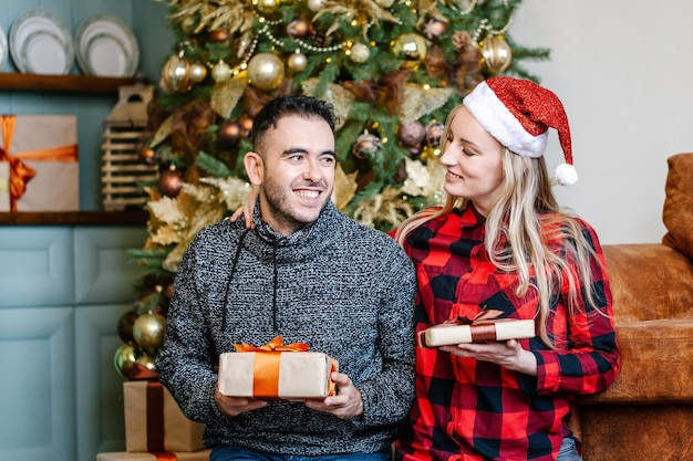 Positives entzücktes paar, das sich gegenseitig weihnachtsgeschenke gibt