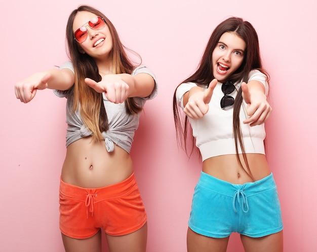 Positives freundporträt von zwei glücklichen mädchen - lustige gesichter, emotionen, lässiger stil, pastellfarben. lächle und sage ok.