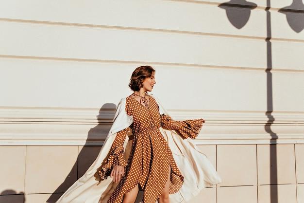 Positives glamouröses mädchen im braunen kleid, das auf der straße tanzt. freudige kaukasische dame, die auf stadt abkühlt.