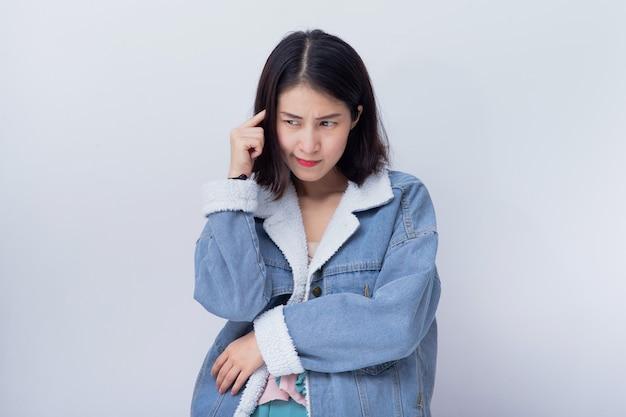 Positives glückliches junges asiatisches mädchen, das blaues porträt der zufälligen kleidung im studio trägt