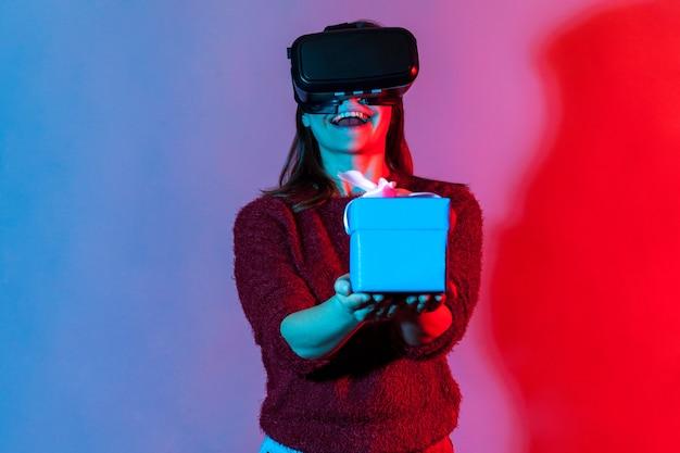 Positives glückliches mädchen in vr-virtual-reality-brille, die verpackte geschenkbox hält und freudig lächelt