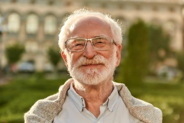 Positives haltungsporträt eines gutaussehenden bärtigen älteren mannes mit brille, der in die kamera schaut und lächelt