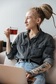 Positives hübsches junges mädchen mit dreadlocks und piercing drinnen mit laptop-computer, der tee trinkt.